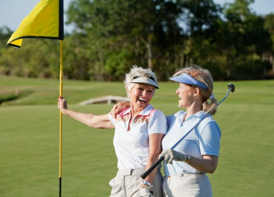 Senior women playing golf.